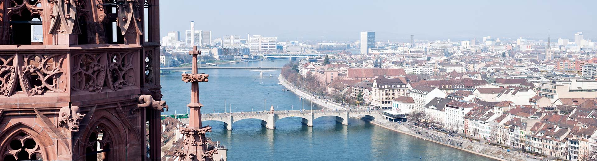 Birds eye view of the Rheine river in Basel on a sunny day, with a tower partially in view on the left and three bridges that cross the river.