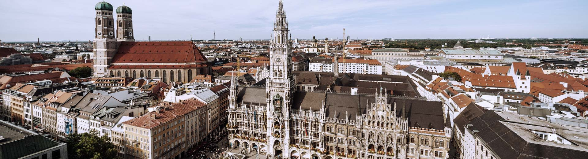 A beautiful town square in Munich on a clear day, with church steeples dominating the skyline