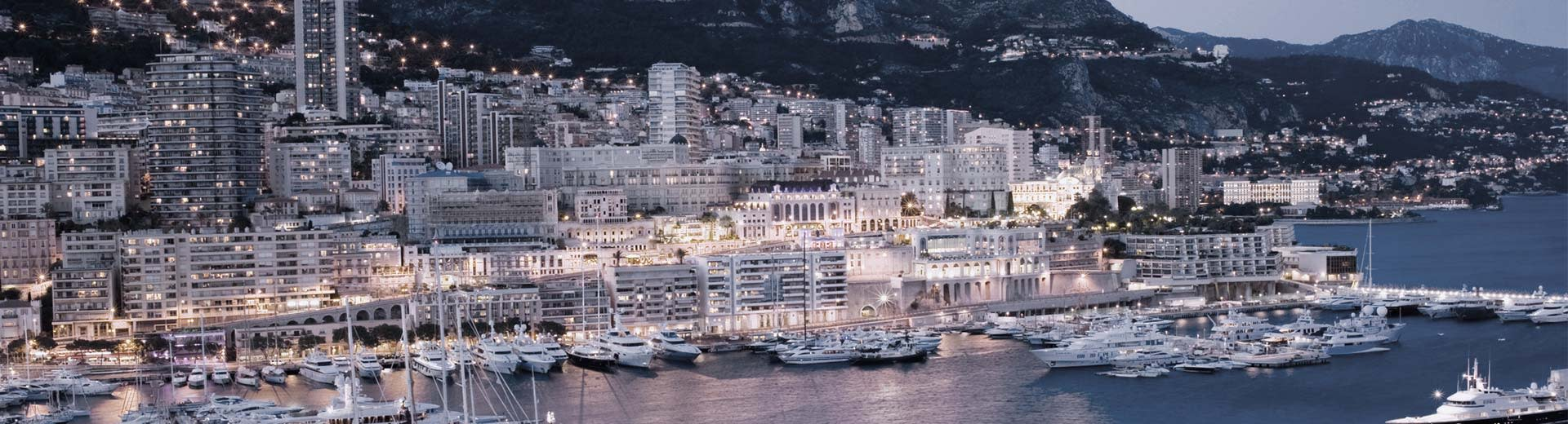 The tightly packed, white buildings of Monaco stretch along the shoreline