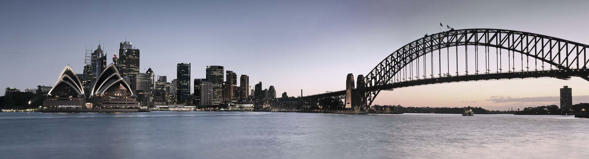 The famous Sydney Opera House dominates this scene, with multiple buildings and the Sydney Bridge on the right hand side