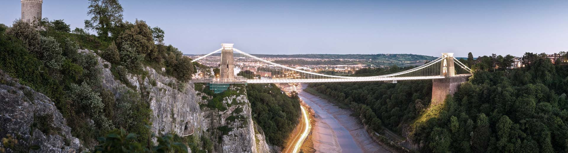 Greenery on a rock cliff to the left with a view of the Clifton Suspension Bridge in Bristol to the center right.