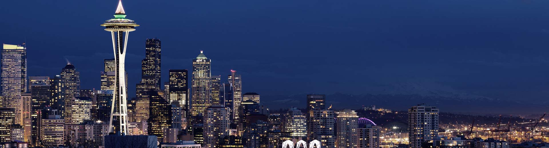 The famous Space Needle of Seattle looms into the nightsky, surrounded by omposing skyscrapers and apartment buildings