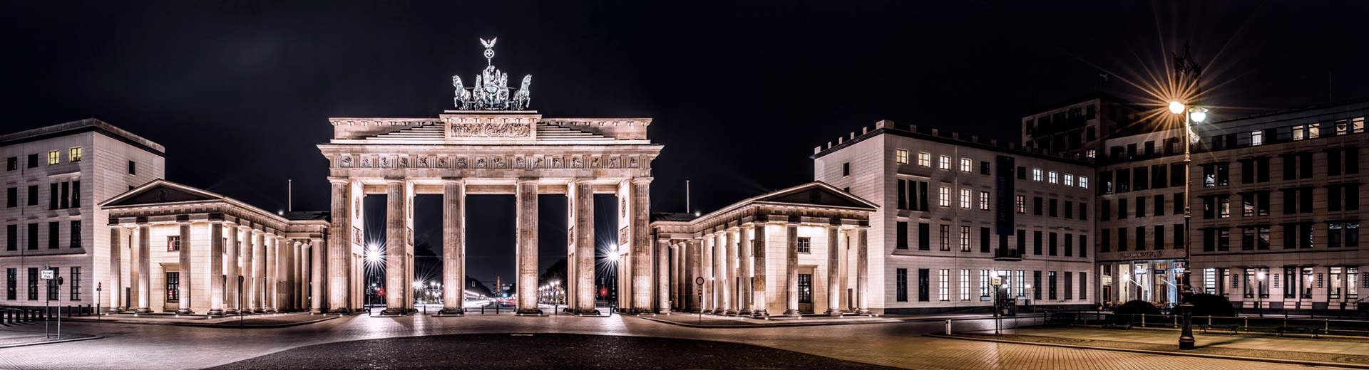 Brandenburg Gate in Berlin at night, with the lights illuminating the structure.