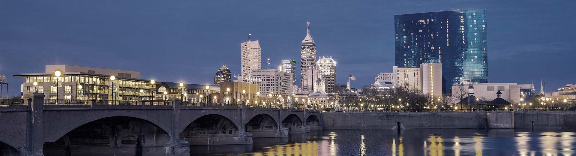 A bridge and skyscrapers lit up against the night sky in Indianapolis