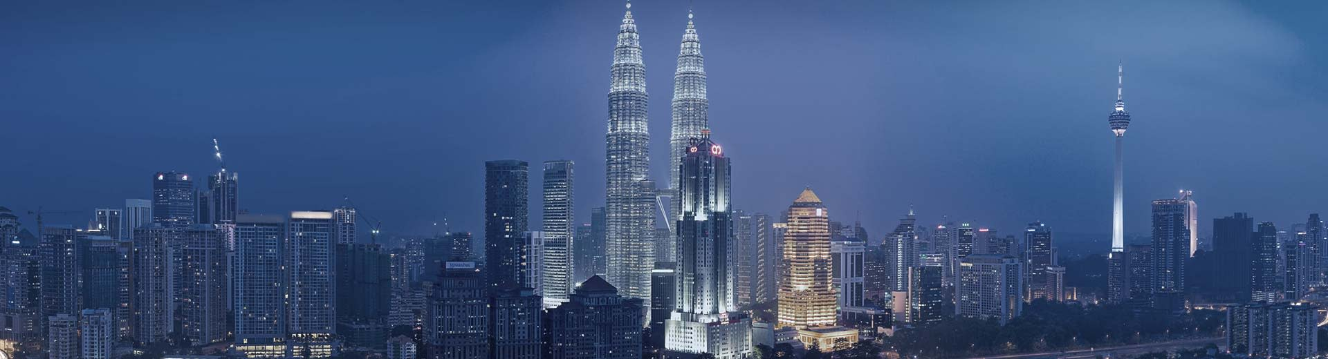 The looming twin towers of Kuala Lumpur light up the dark sky