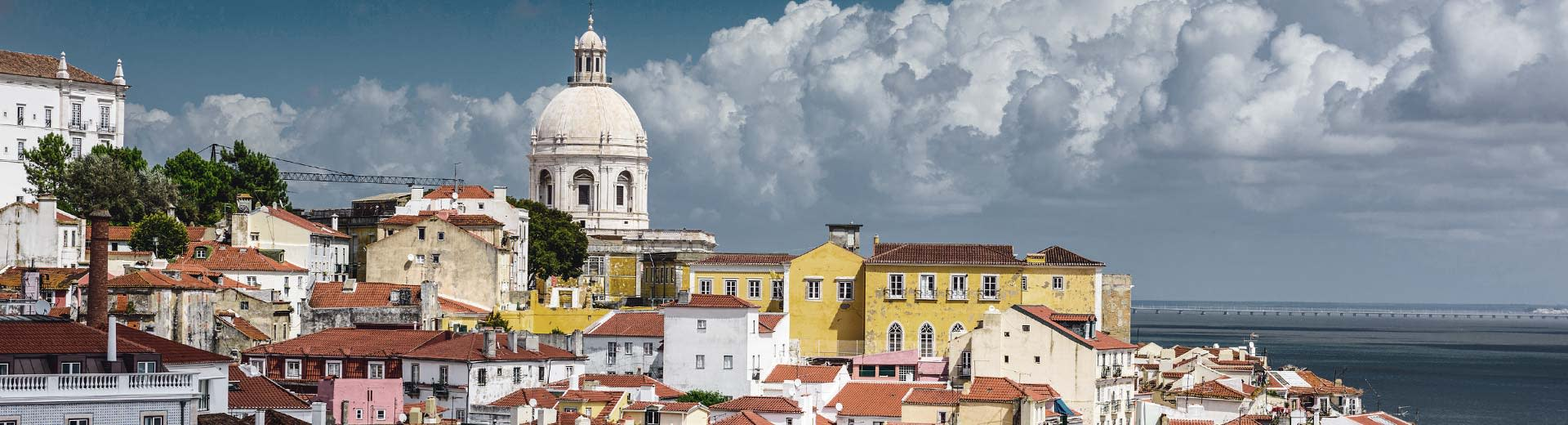 The pastel colored buildigns of Lisbon set against a cloudy sky