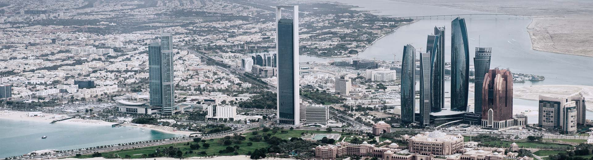 Panorama of Abu Dhabi's city center with a clear view of skyscrapers and desert in the background.