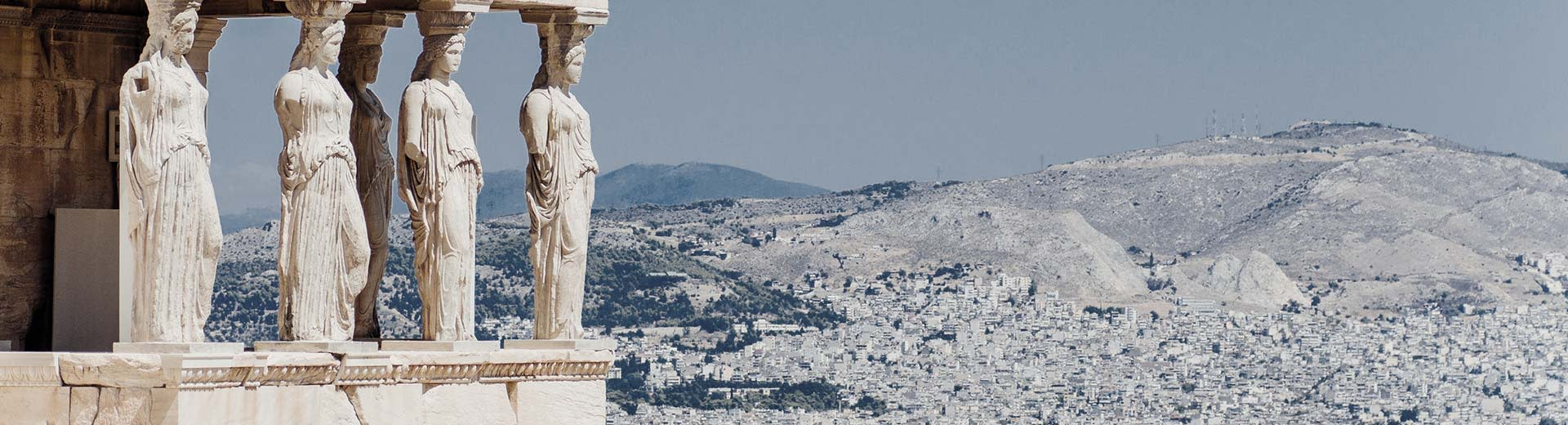 Caryatids of the Erechtheion in Athens with mountains in the background