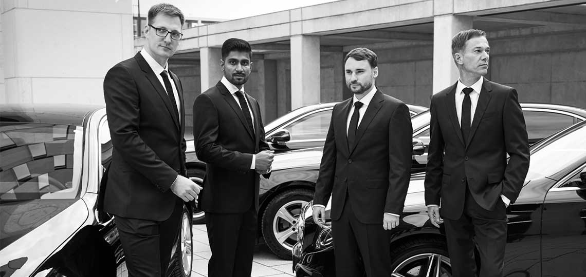 Four real Blacklane chauffeurs stand in front of their fleet of vehicles, coordinating shuttle service for a conference.