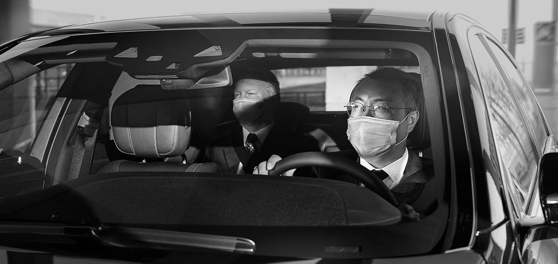 A real Blacklane chauffeur sits behind the wheel, checking in the rearview mirror that the guest is happy. Both are wearing masks.