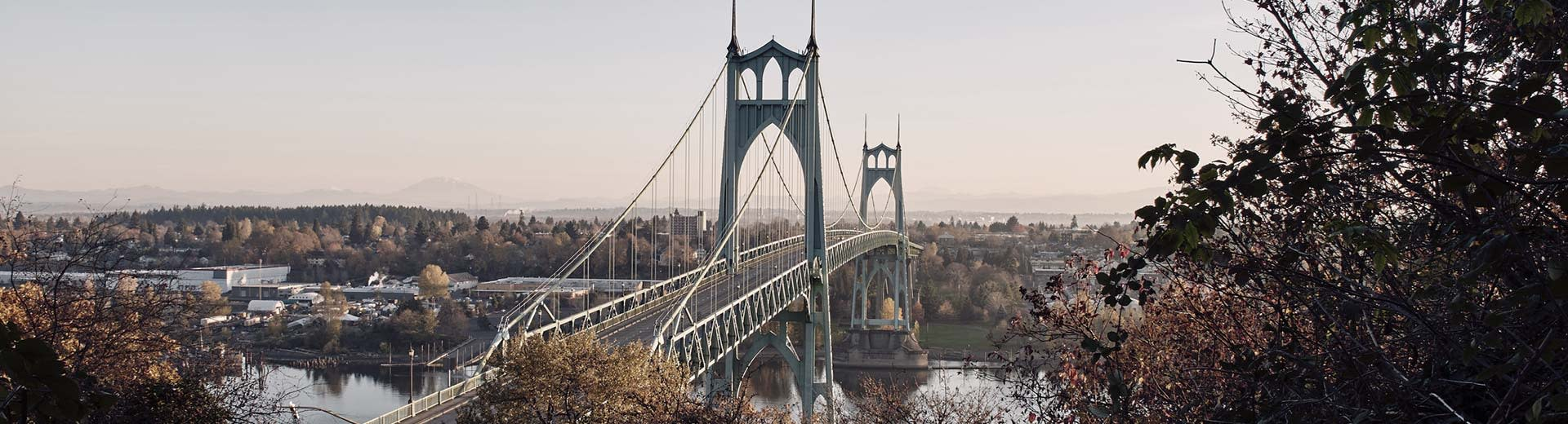 A suspension bridge stretches across a river in Portland, with plenty of trees and green space