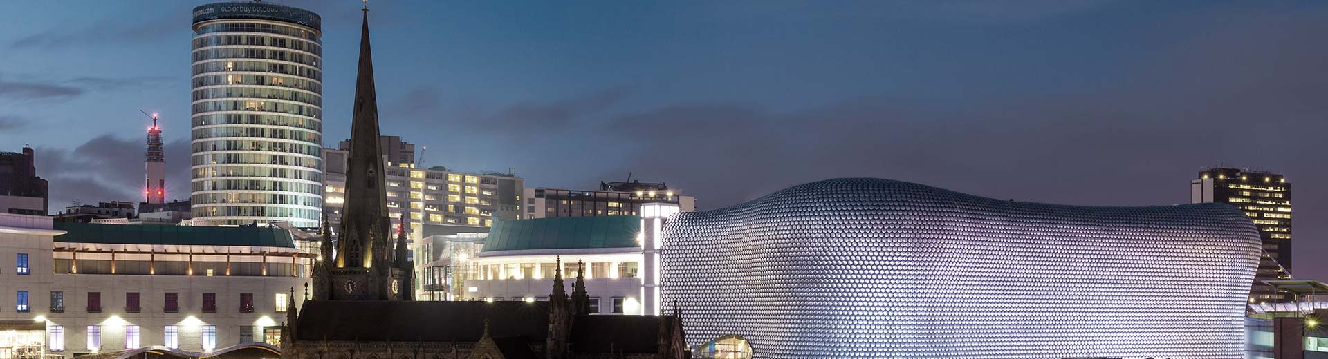 Birmingham city during the evening with the Bull Ring on the right and a church on the left