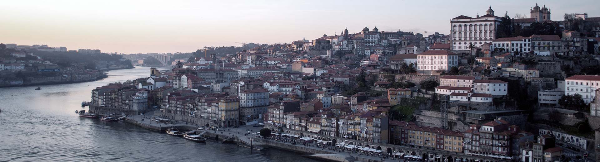The beautiful city of Porto, with historic buildings set against a grey sky and flowing river