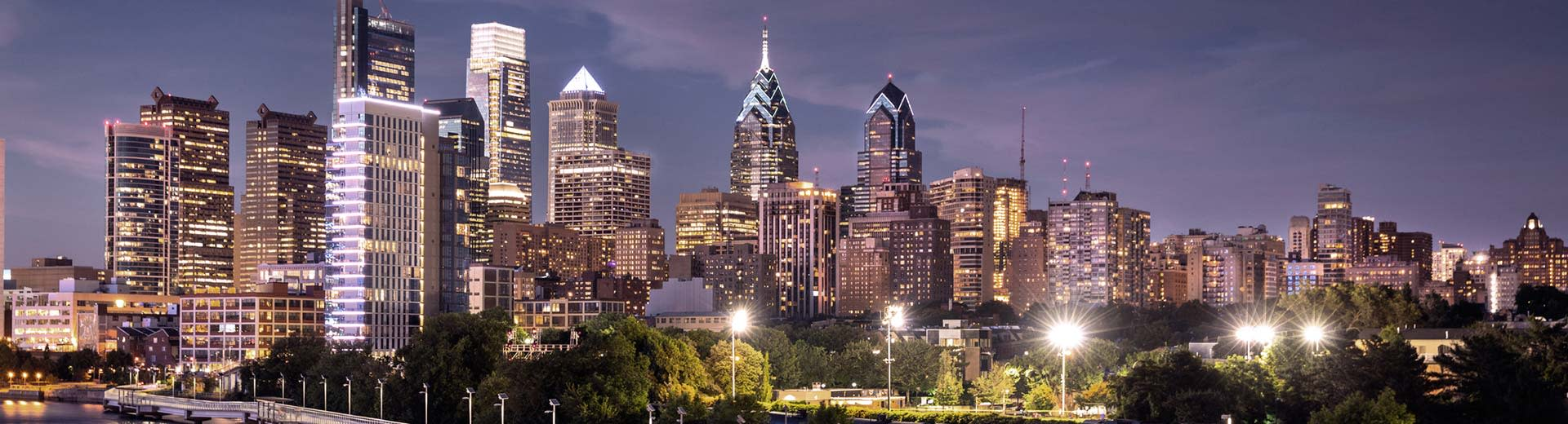 The high-rising Philadelphia skyline at night illuminates the dark sky above