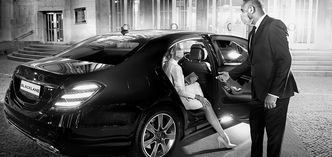 Outside a fancy venue, a real Blacklane chauffeur extends his hand to help a guest get out of the back seat.