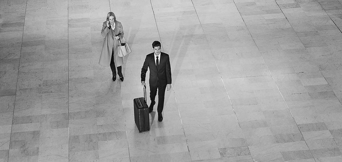 A chauffeur in a suit takes the guest's luggage and guides her out of the airport while she makes a phone call.