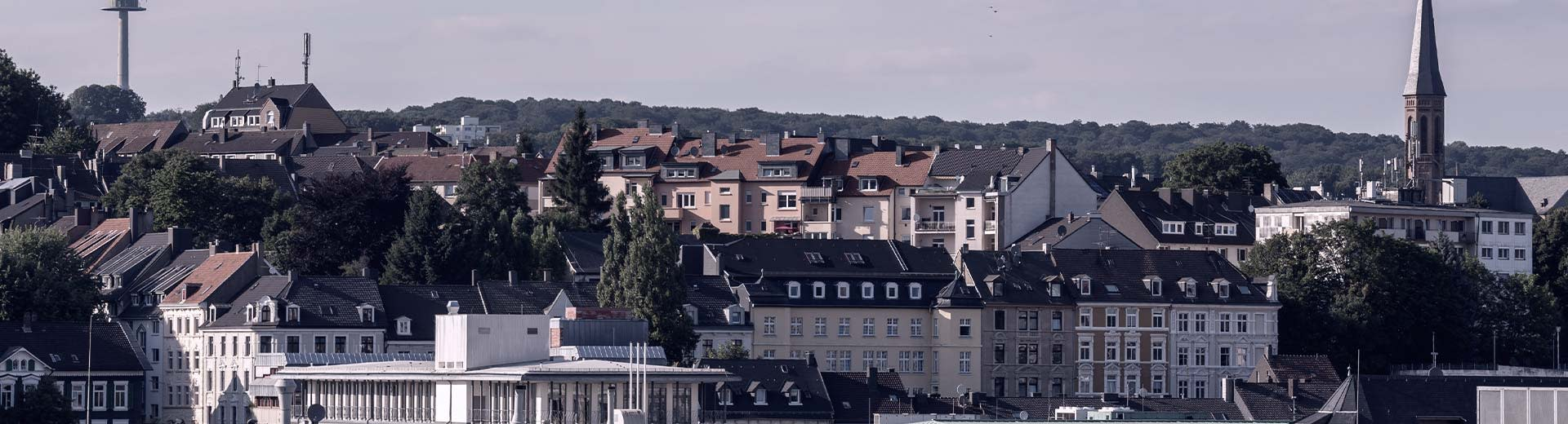 A medley of typical Wuppertal residential buildings in the foreground is contrasted by green hills in the distance