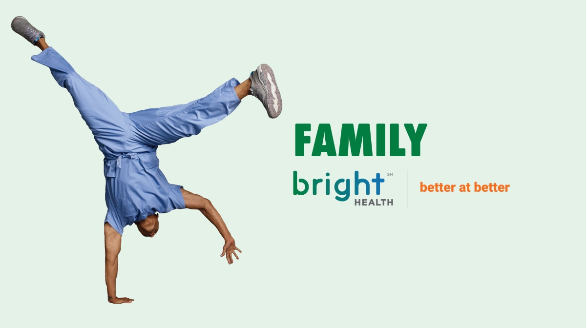 Bright health default image for the family category. Man in scrubs doing a one handed handstand.