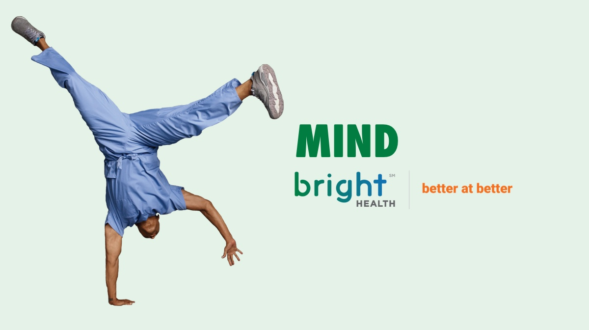 Bright health default image for the mind category. Man in scrubs doing a one handed handstand.