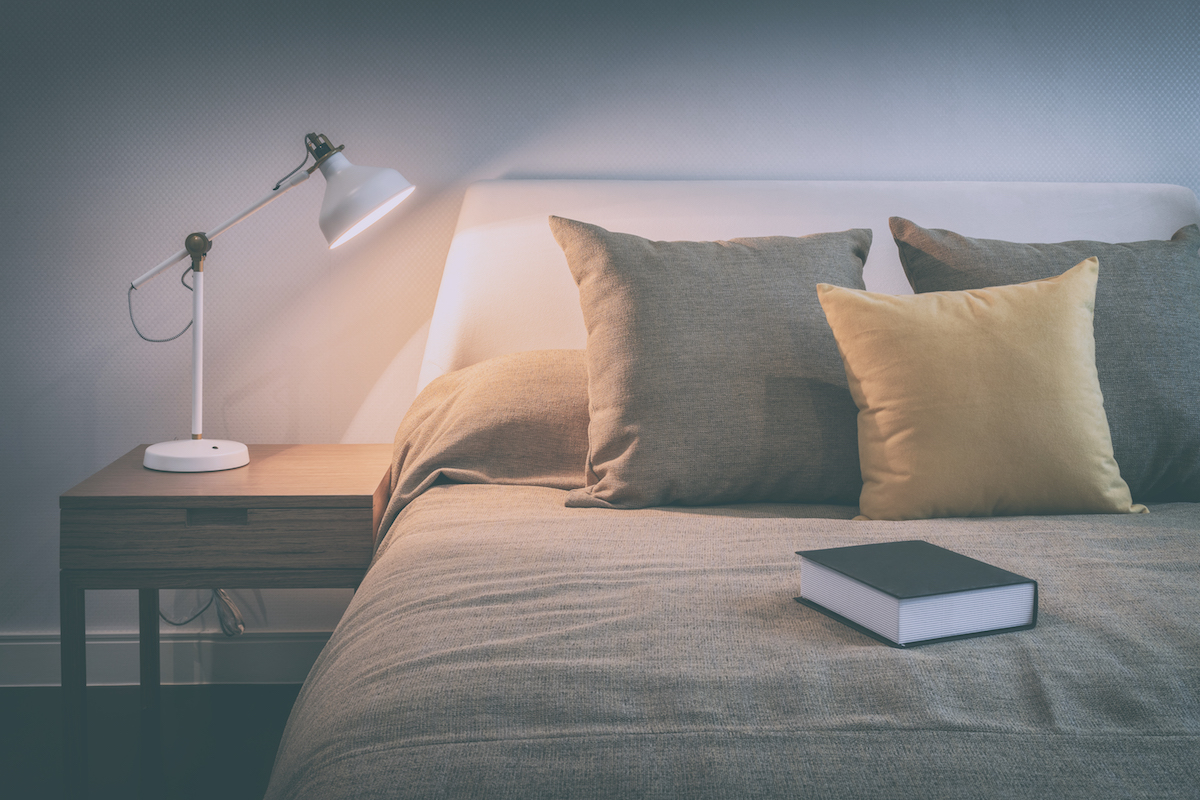 cozy-bedroom-interior-with-book-and-reading-lamp-530931632.jpeg
