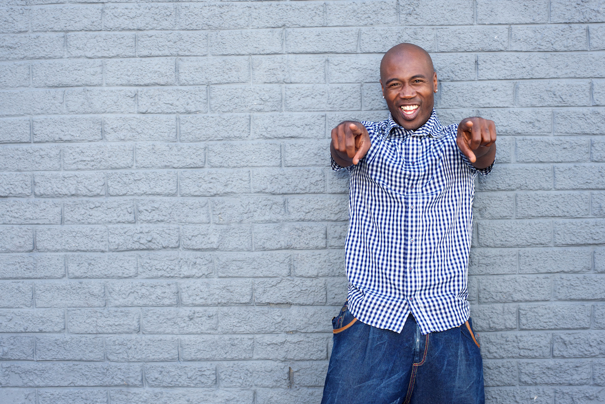 Portrait of cheerful young African-American man pointing finger