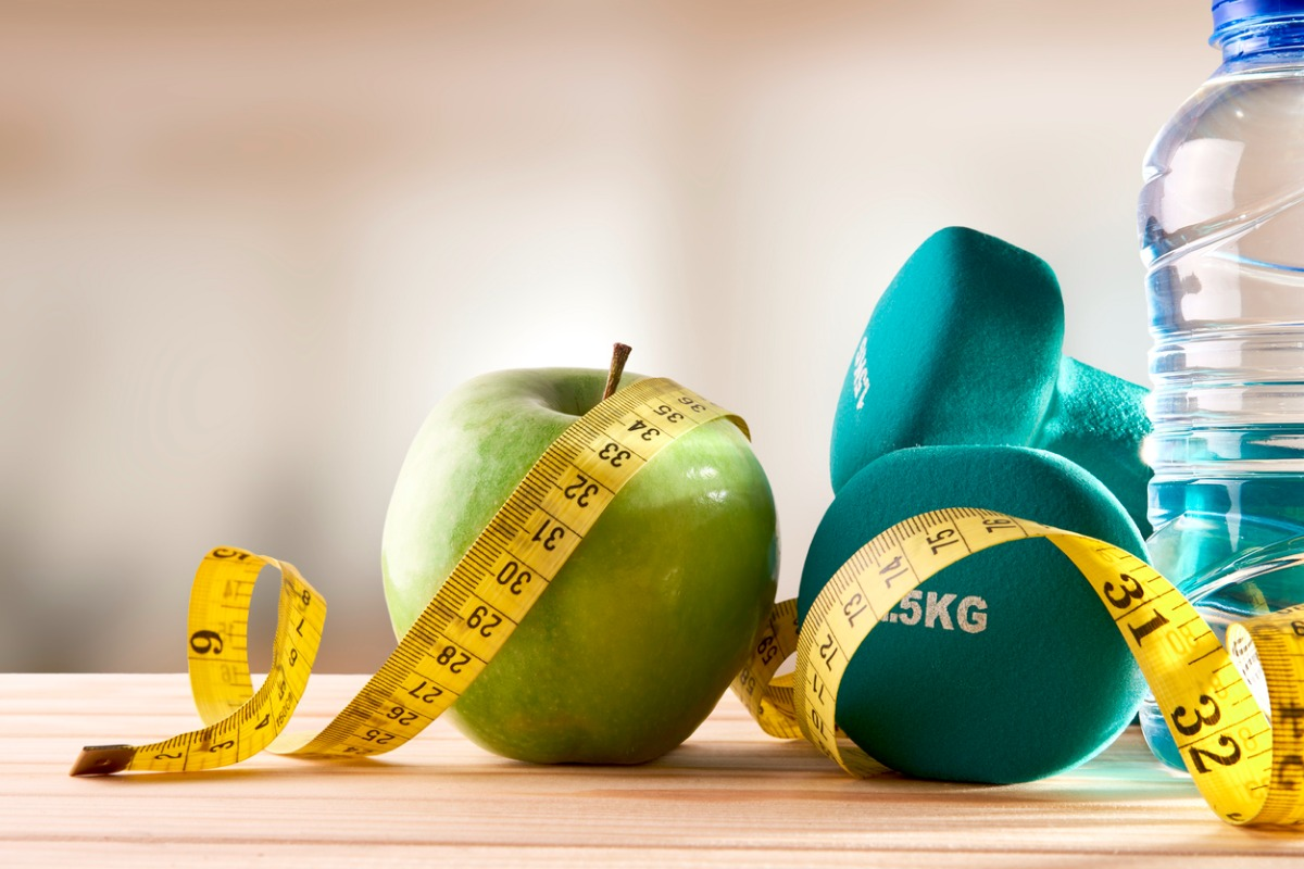Collection of health items: apple, measuring tape, weights and water