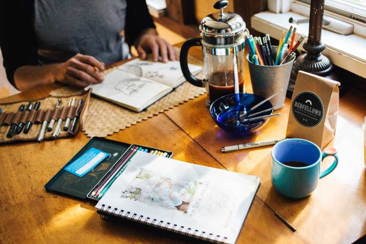 Two sketchbooks on a table next to a coffee mug, drawing utensils, with a person about to draw on one of the sketchbooks. |
