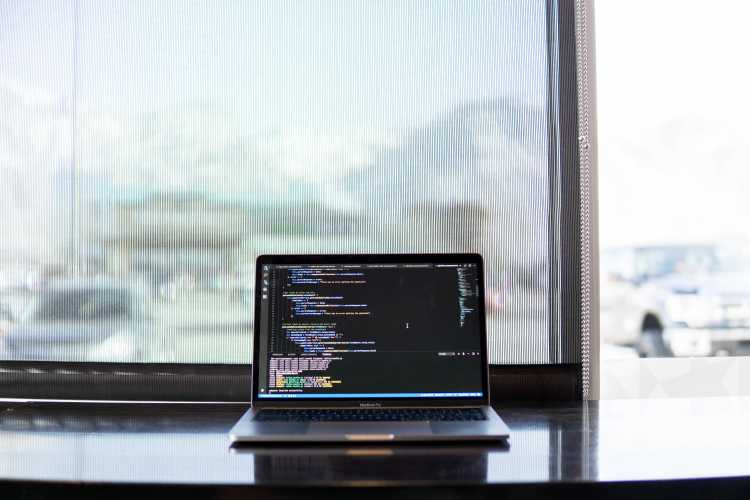 MacBook with Code | Picture of a MacBook with code on it in front of a window with mountains in the background