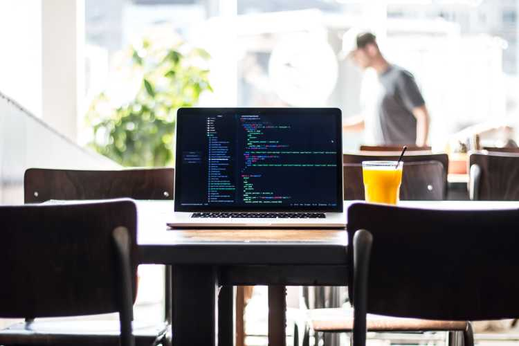 MacBook Pro with code on the screen sitting on a wooden table with two chairs | A picture of a MacBook Pro with code on the screen sitting on a wooden table with two chairs