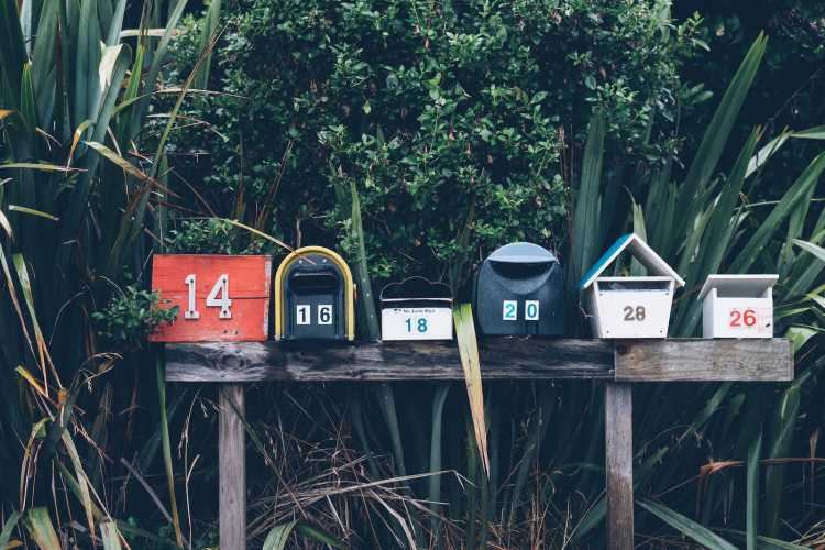 A row of six mailboxes in front of a bush | A row of six mailboxes in front of a bush