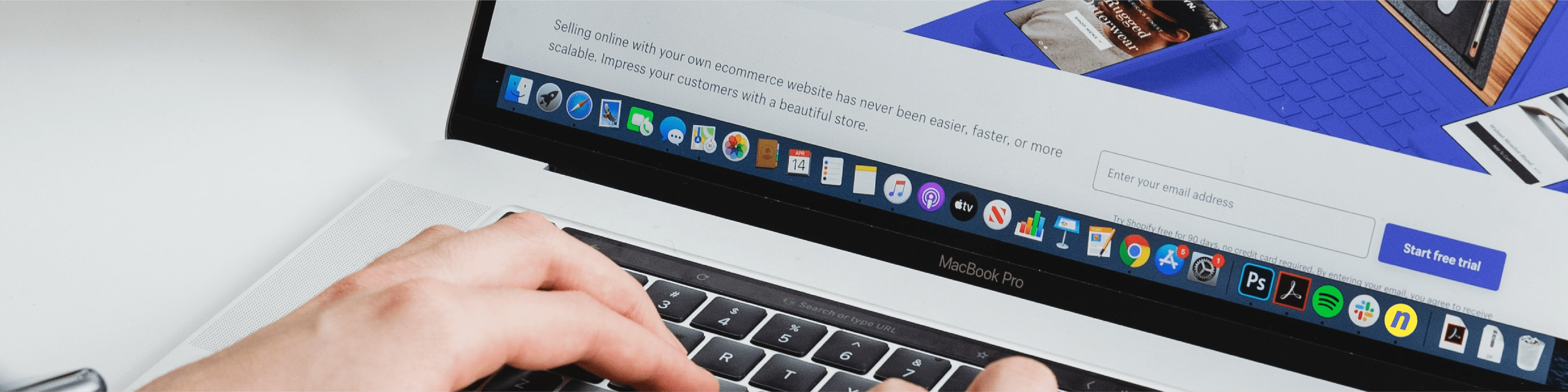 Web marketing banner showing hands typing on a MacBook Pro