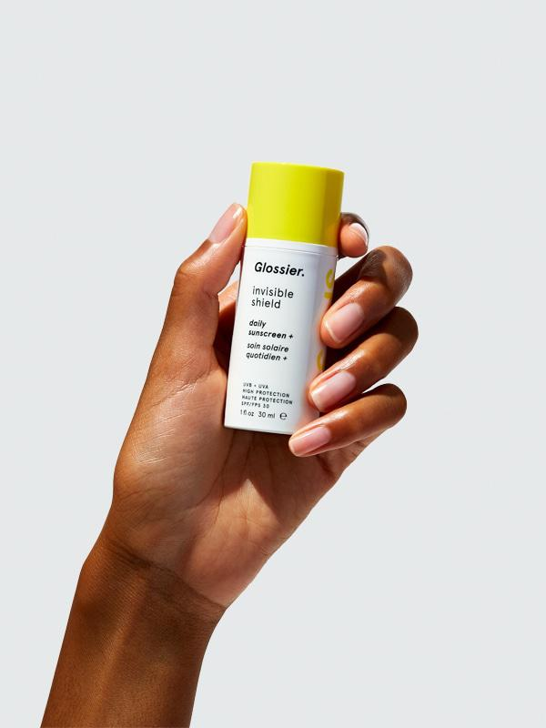 A hand holding a bottle of the Glossier Invisible Shield sunscreen.