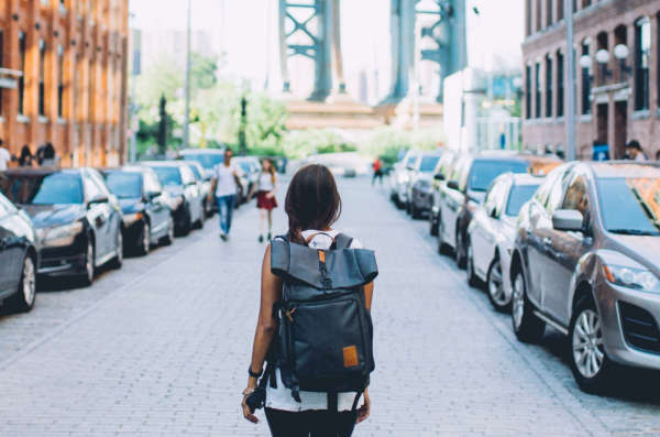 Woman with backpack stands in street with cars parked on both sides