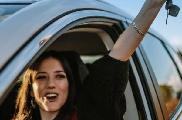 Happy young driver holds keys up in the air