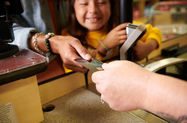 Smiling child watches a parent complete a transaction at a store register