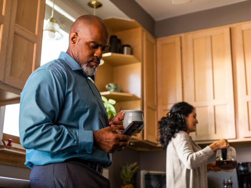 Man in kitchen holding coffee and looking at phone while woman pours coffee