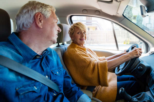 Senior driver smiles at her husband in the passenger seat