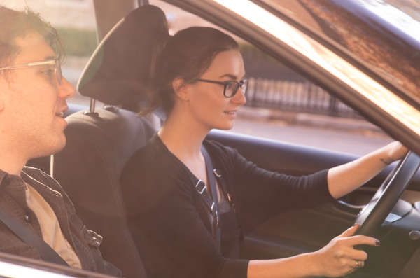 Woman with glasses has both hands on the wheel