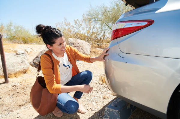 Woman kneels to inspect a dent in rear bumper.