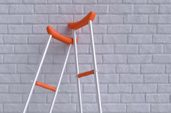 Orange crutches lean on white wall