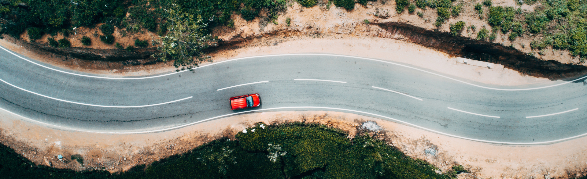 Seen from above, a red car drives on a curving road.