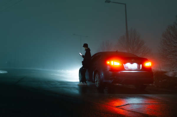 A person stands outside their car looking at their phone on a foggy night