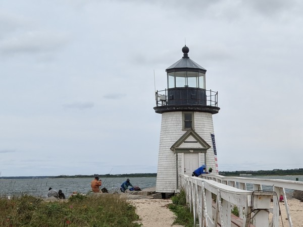 Small historic lighthouse with fishermen working beside it