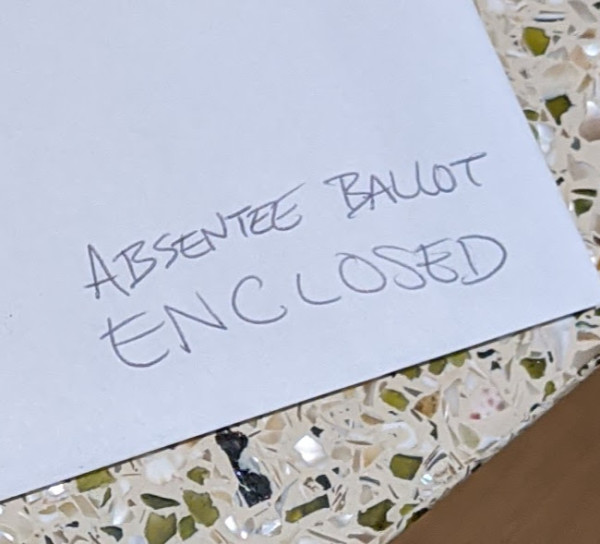 "An envelope with a handwritten note: ""Absentee Ballot Enclosed"""