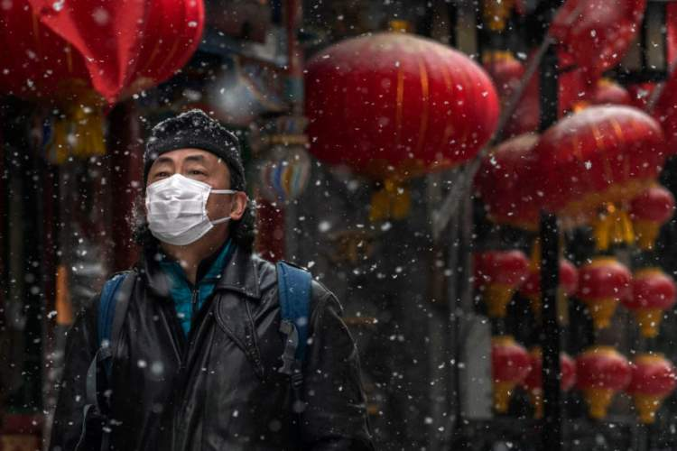 A Chinese man wears a protective mask as he walks during a snowfall in an empty and shuttered commercial street on February 5, 2020 in Beijing, China.