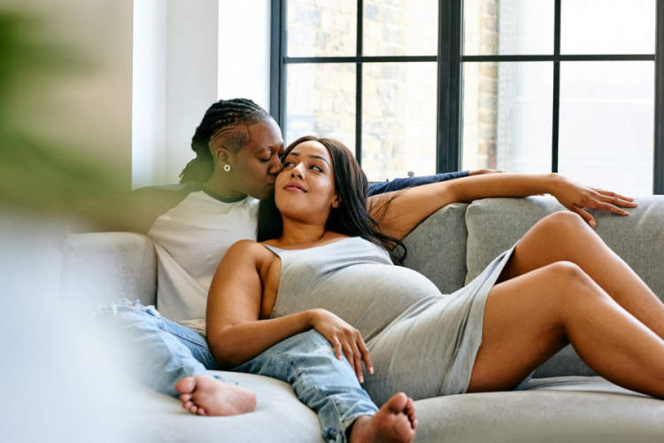 pregnant woman and partner cuddling on couch
