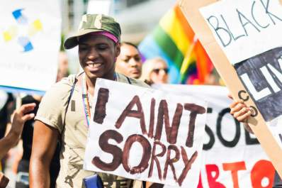 "Smiling man holding a banner reading ""I AIN'T SORRY"" during Stockholm Pride Parade"