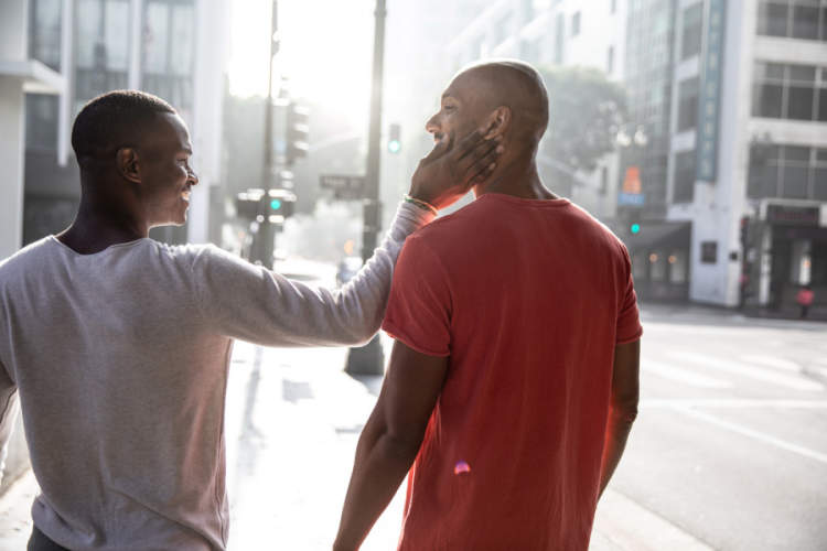 two black gay men being affectionate on city street