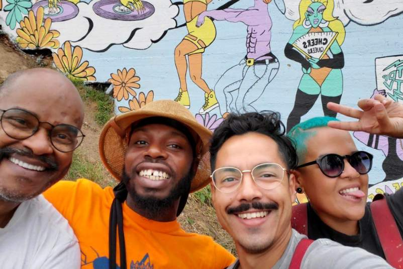 John Burnett, Ajmal Millar, Andres Palacio, and Lisette Correa in front of the mural Transformation Tunnel.