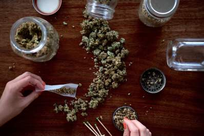 person rolling joint, focus on hands, cannabis on table